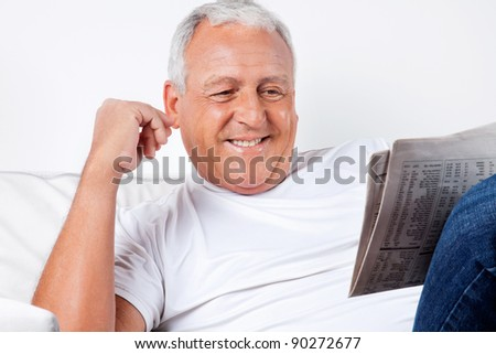 Smiling senior man reading newspaper at home - stock photo
