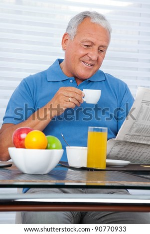 Smiling senior man reading newspaper while having breakfast at home - stock photo