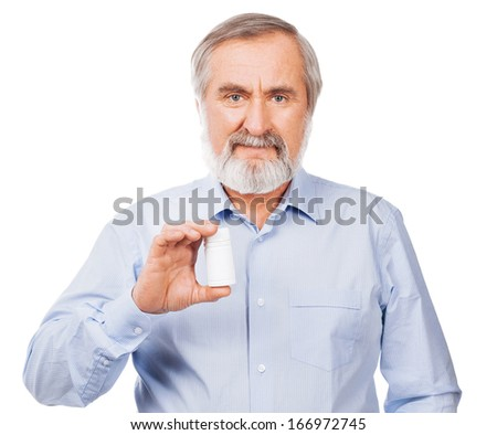Smiling senior man showing pills isolated on white