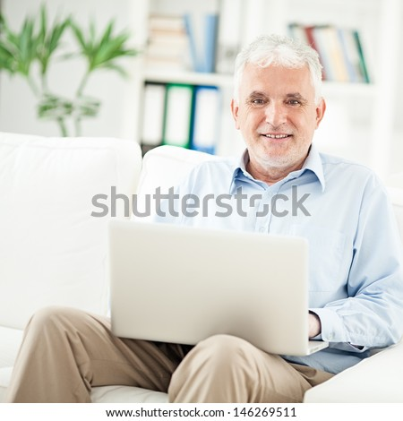 Smiling senior man sitting in his living room and using his laptop. - stock photo