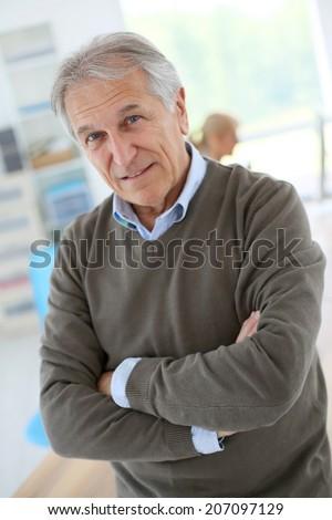 Smiling senior man sitting in office - stock photo