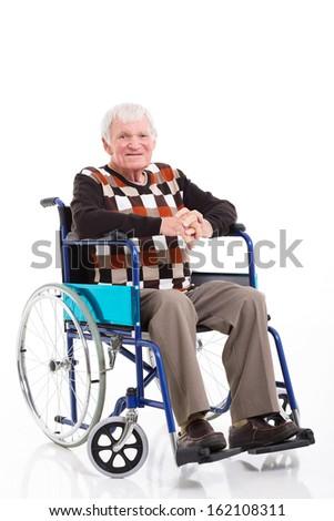 smiling senior man sitting on a wheelchair isolated on white  - stock photo