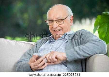 Smiling senior man text messaging through mobile phone at nursing home porch - stock photo