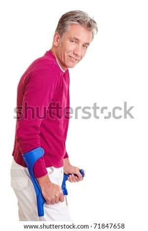 Smiling senior man walking with two crutches - stock photo