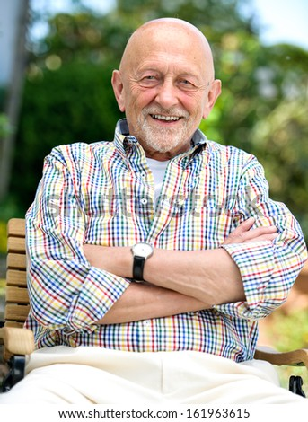 Smiling senior man with arms crossed outdoors - stock photo