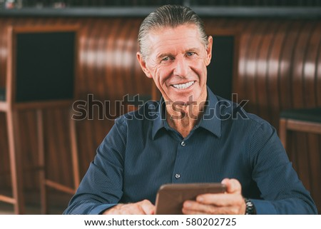 Smiling Senior Man with Digital Tablet in Cafe