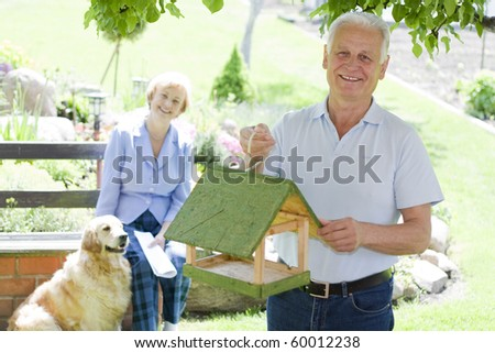 Smiling senior man with his wife in the background - stock photo