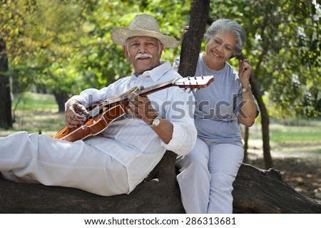Smiling senior man with woman having fun at park while playing guitar - stock photo