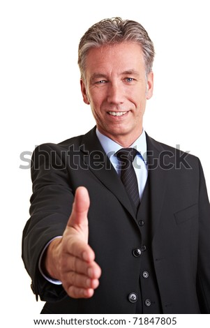 Smiling senior manager offering his hand for a handshake - stock photo
