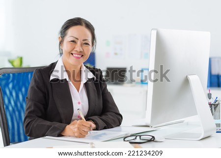 Smiling senior manager working with papers - stock photo