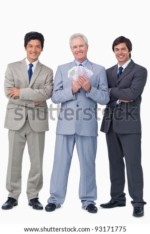 Smiling senior salesman with money and employees against a white background