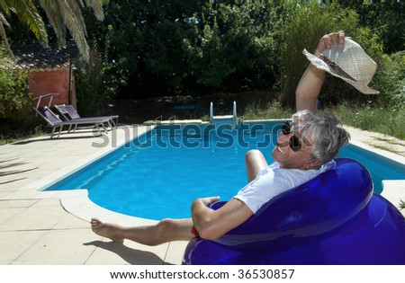 Smiling senior sitting by a swimming pool on a blue inflatable chair. - stock photo