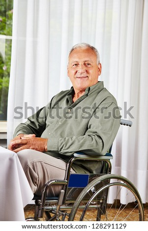 Smiling senior sitting in a wheelchair in a nursing home - stock photo