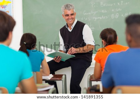 smiling senior teacher teaching group of high school students in classroom - stock photo