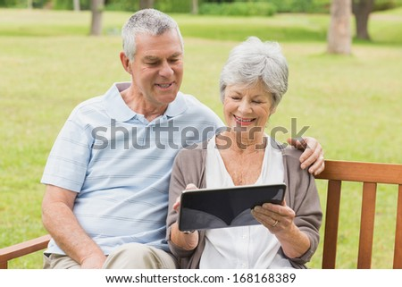 Smiling senior woman and man using digital tablet on bench at the park - stock photo