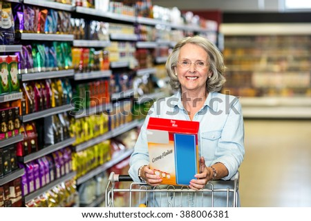 Smiling senior woman buying cereals at the supermarket