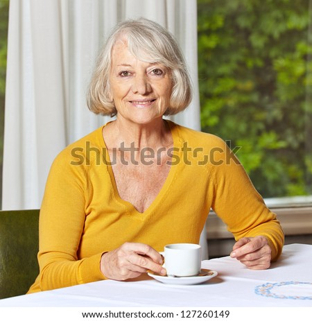 Smiling senior woman drinking a cup of coffee in a retirement home - stock photo