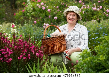 smiling senior woman gardener with horticultural tools working with pink flowers in garden