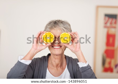 Smiling senior woman holding half oranges over eyes against white background - stock photo