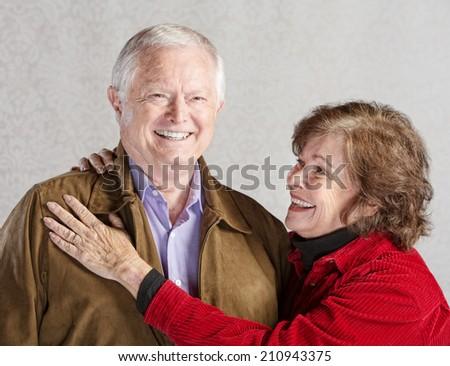 Smiling senior woman holding her happy husband - stock photo