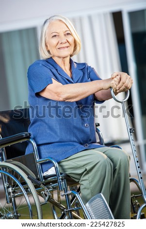 Smiling senior woman holding walking stick while sitting on wheelchair at nursing home yard - stock photo