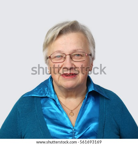 Smiling senior woman in glasses on gray background - grandmother portrait
