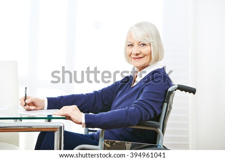 Smiling senior woman in wheelchair on a table doing memory training - stock photo