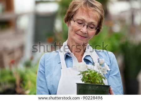 Smiling senior woman looking down at potted plant