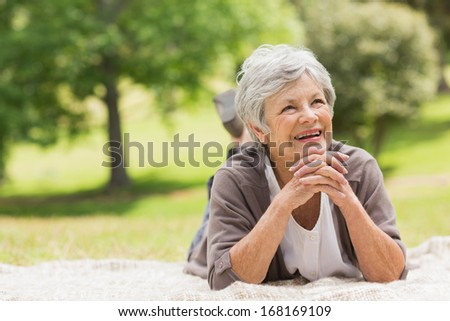 Smiling senior woman looking up while lying at the park - stock photo