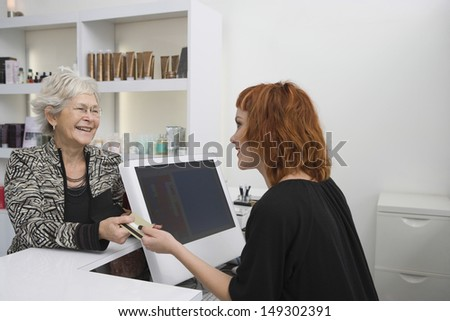 Smiling senior woman paying for her haircut through credit card at reception desk - stock photo