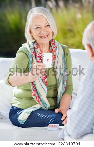 Smiling senior woman playing cards with man at nursing home porch - stock photo