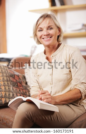 Smiling senior woman reading a book at home - stock photo