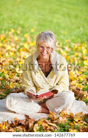 Smiling senior woman reading book while sitting in park - stock photo