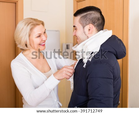 Smiling senior woman seeing off young boyfriend at doorway - stock photo