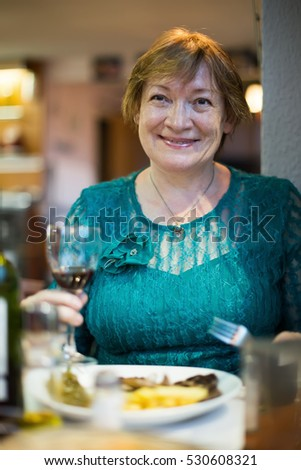 Smiling senior woman sitting in restaurant and having cold beverage