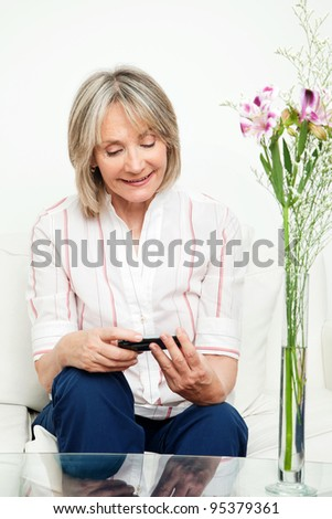Smiling senior woman sitting on couch with smartphone