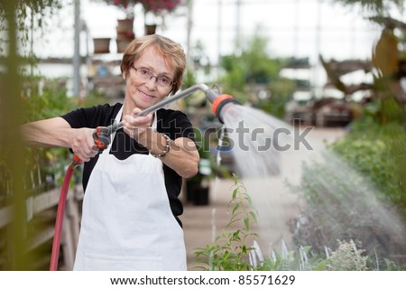 Smiling senior woman spraying water on plants