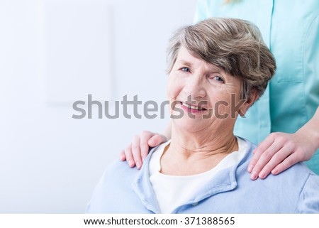 Smiling senior woman supported by caregiver or nurse - stock photo