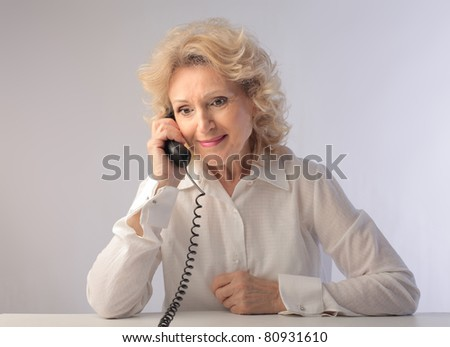 Smiling senior woman talking on the telephone - stock photo