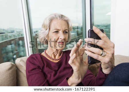 Smiling senior woman text messaging on smart phone at home