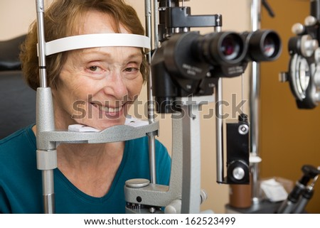 Smiling senior woman undergoing eye examination test with slit lamp in store - stock photo