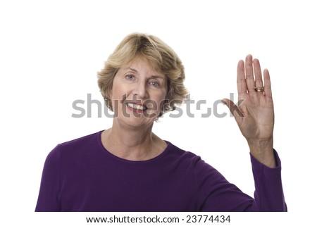 Smiling senior woman with left hand raised - stock photo
