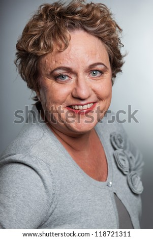 Smiling senior woman with short curly hair. Studio shot against grey.