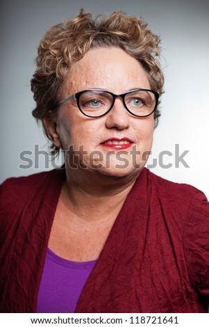 Smiling senior woman with short curly hair. Wearing glasses. Studio shot. - stock photo