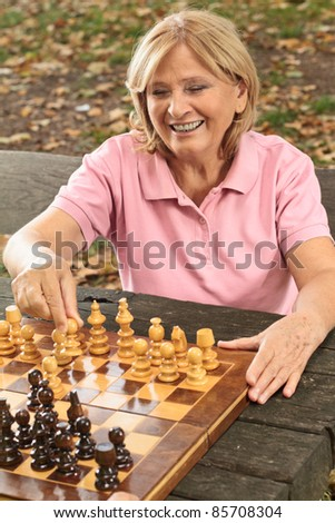 Smiling senior women playing chess on a park bench.