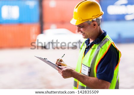 smiling senior worker working at harbor - stock photo