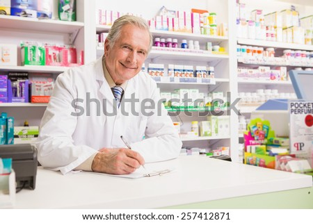 Smiling senior writing on clipboard in the pharmacy - stock photo