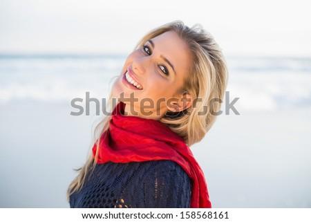 Smiling sensual blonde posing on a beautiful wild beach - stock photo