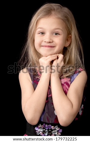 Smiling seven year old blonde girl in a dress looking directly standing put her hands to the face on a black background - stock photo