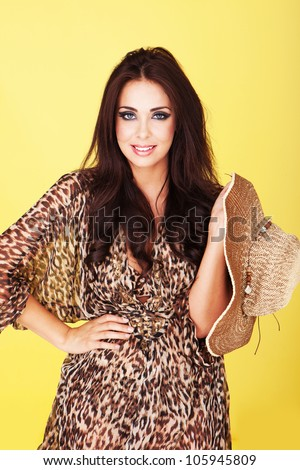 Smiling sexy brunette in sheer outfit with an animal print pattern dangling a wide brimmed straw hat over her shoulder - stock photo